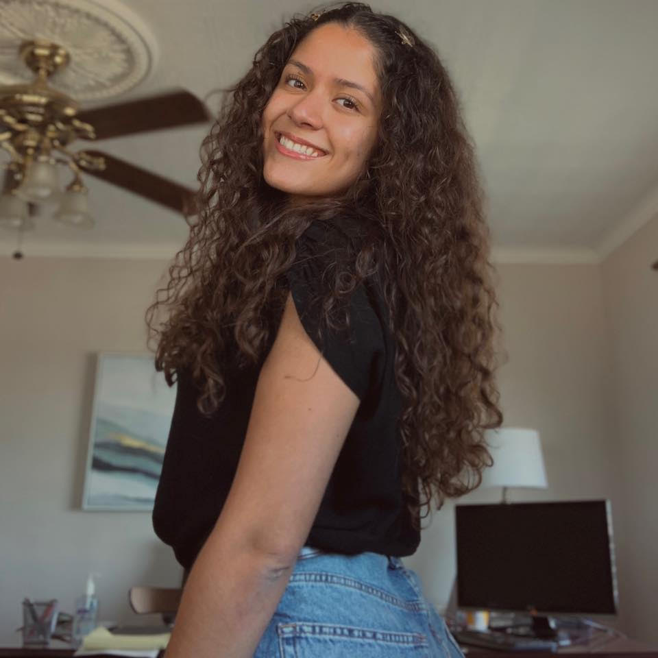 Image of Nataly Esparza looking at the camera over her left shoulder. She is wearing a black short-sleeved top and jeans.